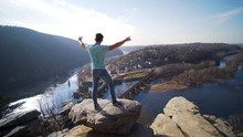 Young Man Stands On A Rock And...