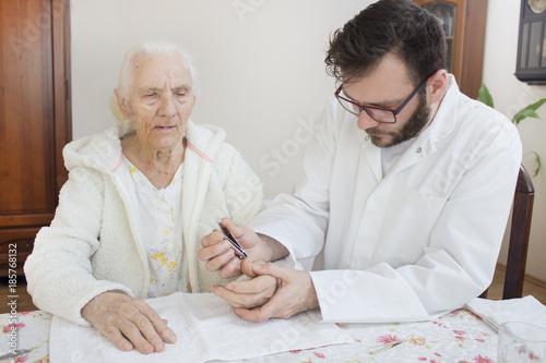 Fototapeta Zabieg pielęgnacyjny dłoni bardzo starej kobiety. Pielęgniarz obcina paznokcie u rąk starej kobiecie. obraz