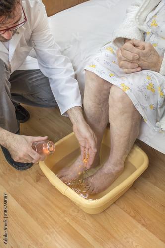 Fotografie, Obraz  Stara kobieta moczy stopy w misce z wodą