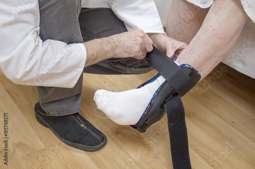 Fotografía  Uraz kostki. Zakładanie stabilizatora na kostkę starej kobiety.