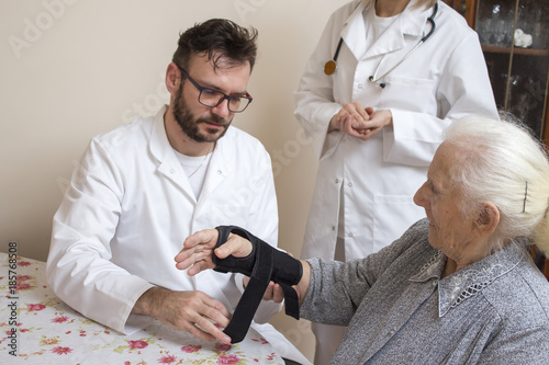 Fotografía  Pielęgniarz w białym kitlu zakłada stabilizator na nadgarstek starej kobiety przy nadzorze lekarza
