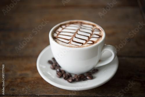 Fotobehang Koffiebonen White coffee mug on patterned old wooden floor.