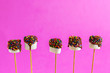canvas print picture - marshmallows on a sticks on pink background. glazed with chocolate and colorful sprinkles.