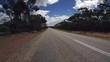 Gerade Fahrstrecke mit teilweise bewölktem Himmel in einem PKW auf einem Highway in West-Australien mit Kamerablickwinkel nach vorne