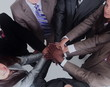 Group of business people putting their hands on top of each othe