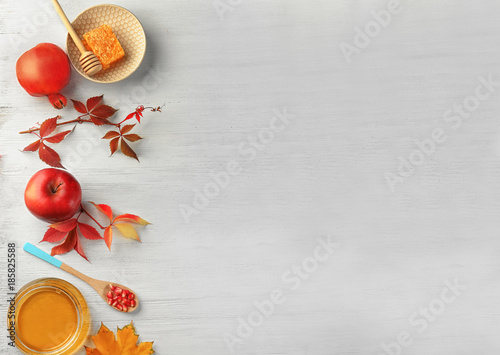 Composition with honey, apple and pomegranate for Rosh Hashanah holiday on white wooden background, top view