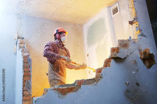 Fotografie, Obraz  worker with sledgehammer at indoor wall destroying