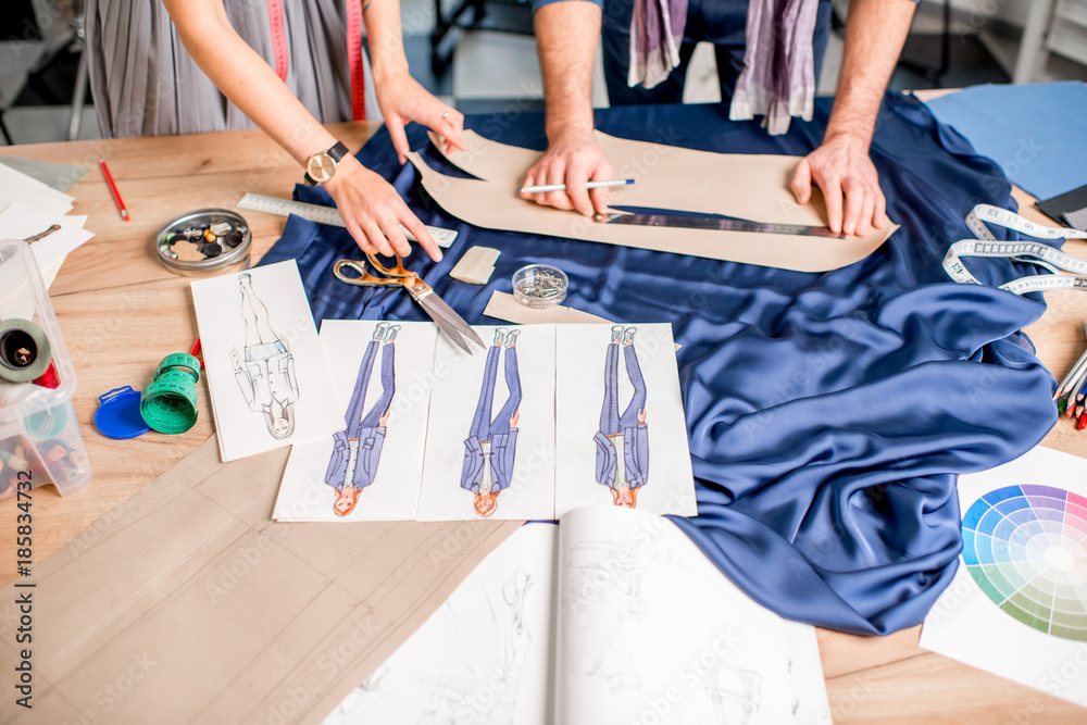 Fototapeta Cutting blue fabric on the table full of tailoring tools. Close-up view on the hands, fabric and fashion drawings
