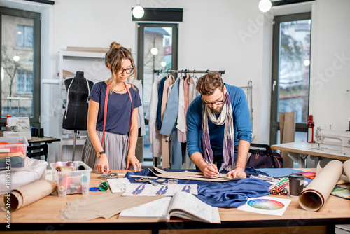 Couple Of Fashion Designers Working With Fabric At The Studio Full Of Tailoring Tools And Equipment Buy This Stock Photo And Explore Similar Images At Adobe Stock Adobe Stock