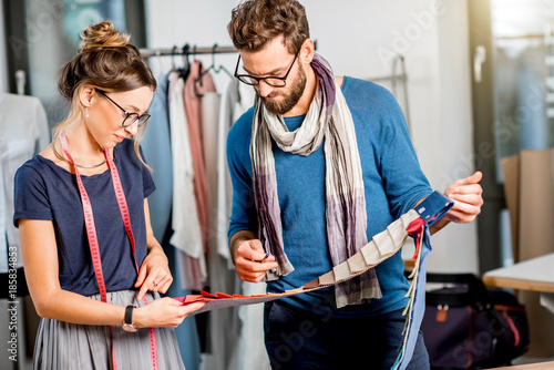 Couple Of Fashion Designers Choosing Fabric Standing At The Studio Full Of Tailoring Tools And Equipment Wall Mural Rh2010