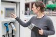 canvas print picture - Frau waehlt Ladevorgang fuer Elektoauto aus