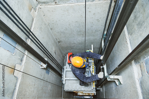 Photo lift machinist repairing elevator in lift shaft