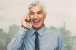 Cheerful senior businessman talking on cellphone