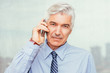 Confident senior businessman with mobile phone