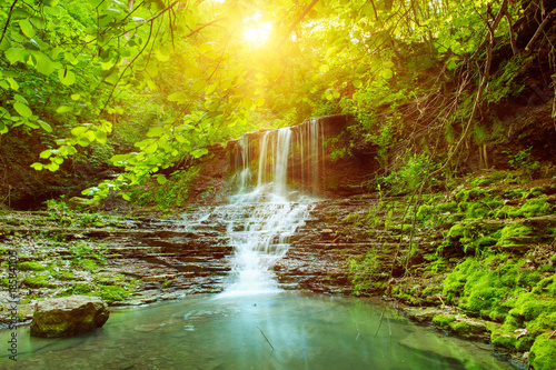 Keuken foto achterwand Watervallen Beautiful mountain rainforest waterfall with fast flowing water and rocks, long exposure. Natural seasonal travel outdoor background with sun shihing