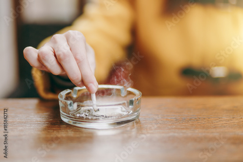 Focus on caucasian young woman hand putting out cigarette on glass ashtray on wooden table, cigarette butt, smoking is dying Wallpaper Mural