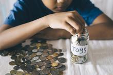 Young Asian Boy Putting Coins Into Glass Jar. Saving Money To Buy Toys. Saving Concept