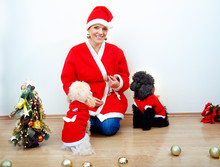 Cheerful Young Woman In Christmas Outfit Accompanied By Two Sweet Poodles.