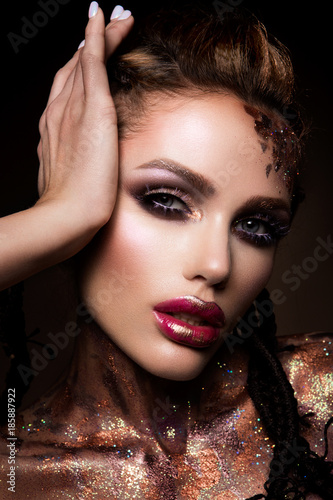 Tela  Fashion model with bright makeup and colorful glitter and sparkles on her face a
