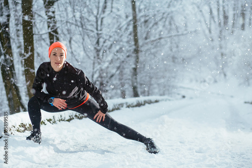 Poster Glisse hiver Active american woman exercising outdoors in a park in fresh white winter snow doing stretching exercises to warm up as she smiles at the camera, real snowfall, flash light with copy space.