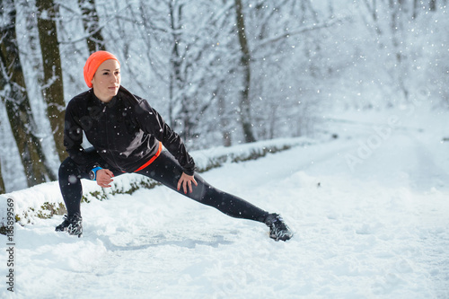 Cadres-photo bureau Glisse hiver Outdoor sport exercises, sporty motivation concept. Woman jogger wearing black sportswear training exercising stretching legs outside in winter.