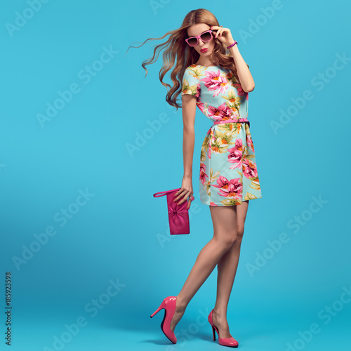 Fashion. Blond Woman in fashion pose. Young beauty Lady in Floral Dress, Trendy Hairstyle, fashion Pink Heels, Glamour Clutch. Playful Girl, Spring Summer Outfit Wall mural