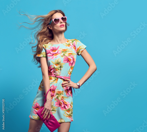 Fashion Young woman in Floral Dress. Trendy wavy Hairstyle. Glamour Sexy Blond Model in fashion pose, Stylish Sunglasses, fashion Clutch. Playful Summer Girl on Blue Wall mural