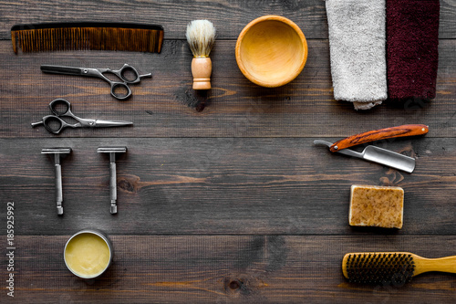 Vintage barbershop tools. Razor, sciccors, brush on dark wooden background top view pattern copyspace