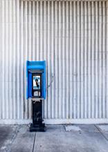 Blue Public Pay Phone Against A White Wall