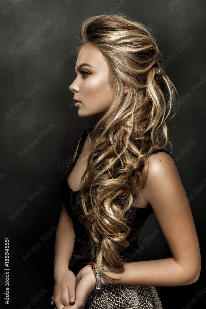 Fototapeta Beautiful girl with long wavy hair. fair-haired model with curly hairstyle and fashionable makeup