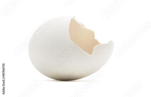 Empty golden cracked egg shell on white.