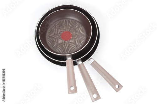 Top view on stack of new frying pans on white background