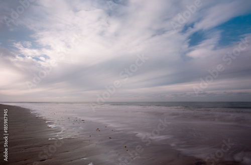 Clouds at Dutch beach with reflections