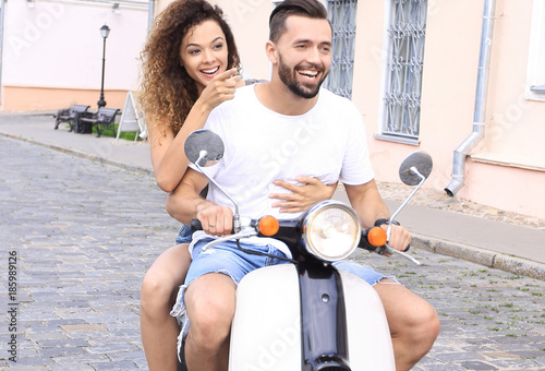 Photographie  Full length side view of happy couple riding on retro motorbike