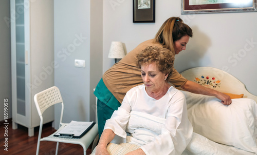 Photo Female caregiver accommodating the pillow to elderly female patient