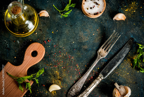 Staande foto Koken Cooking food concept, spices, herb and oil for preparing dinner, with cutting board, table knife and fork, copy space top view frame