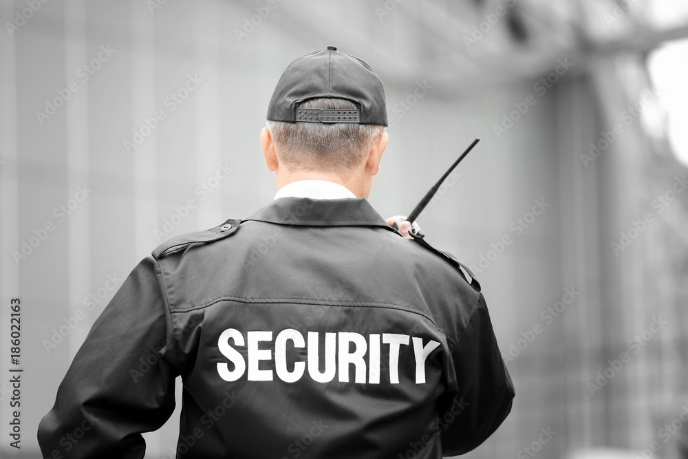 Fototapeta Male security guard using portable radio outdoors