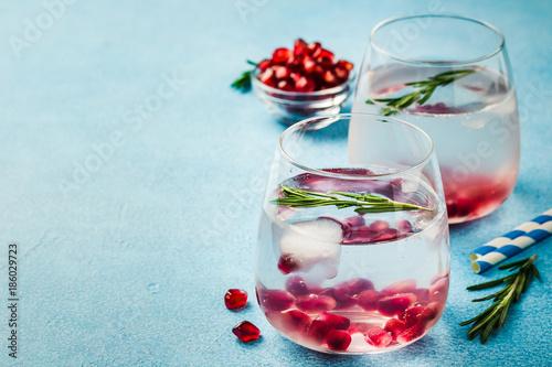 Obraz na plátně  Pomegranate rosemary drink on light blue background