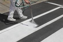Worker Spraying Pedestrian Crosswalk At A Street