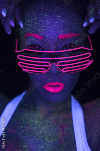 Closeup woman face with fluorescent make up and led lights glasses, creative makeup look great for nightclubs. Halloween party, shows and music concept - 186041592