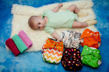 Infant Laying On White, Blue Background Near Colorful Textile Diapers