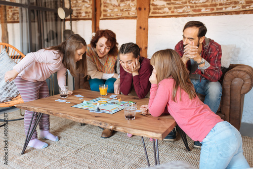 Fotografia, Obraz Happy family at home in the couch playing classic table games .
