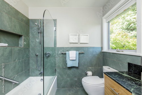 . Beautiful modern bathroom with glass shower  green tiles and black