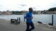 Young man jogging in city near river, super slow motion 120fps