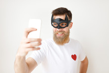 Waist Up Portrait Of Cheerful Bearded Male Model Poses At Smart Phone Camera, Wears Batman Mask And Casual T Shirt, Being Glad To Make Selfie, Isolated Over White Studio Background.