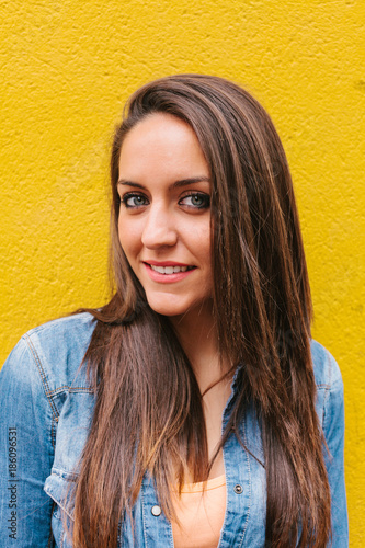 Portrait of a Young Woman in the Street Against a Yellow Wall