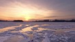 AERIAL: Flight over a frozen river during a blood-red sunset. Colorful landscape, frosty evening, beautiful texture of ice. Fresh ice without snow, crystal sharp ice particles. Winter russian nature.
