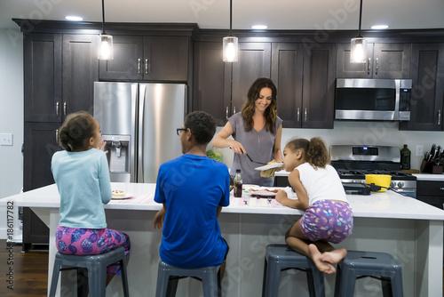 Fotografie, Obraz  Mom cooking breakfast for kids in kitchen