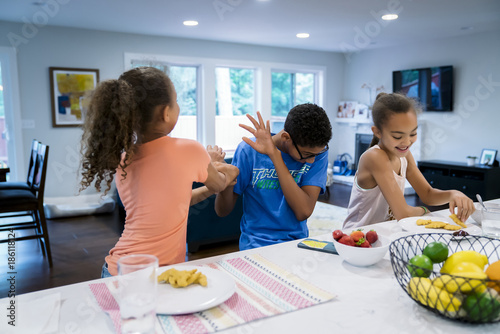 Kids goofing off while eating lunch in kitchen Canvas Print