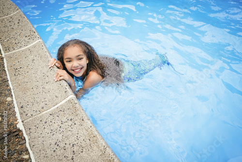 Photographie  Smiling girl with mermaid tail swimming in pool